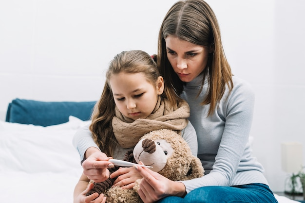 Portrait of mother sitting with her daughter holding teddy bear looking at thermometer Free Photo