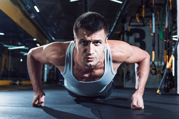 Portrait of a muscular man doing push ups in gym Free Photo