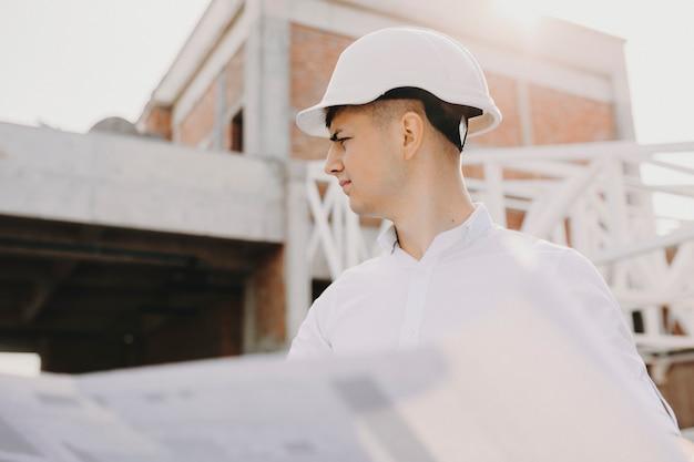 그의 손에 계획으로 그의 건물에서 작업을 검사하는 성인 소유자의 초상화. 프리미엄 사진