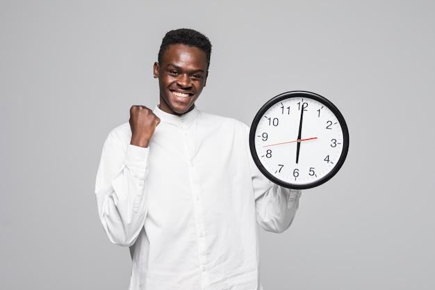 白い背景で隔離の壁時計勝利ジェスチャーを保持しているアフロアメリカンの男の肖像 無料写真
