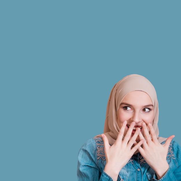 青い背景に驚く女性の肖像画 Premium写真