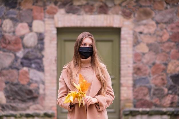 医療フェイスマスクの公園で秋の背景に美しい大人の若い女性の肖像画 Premium写真