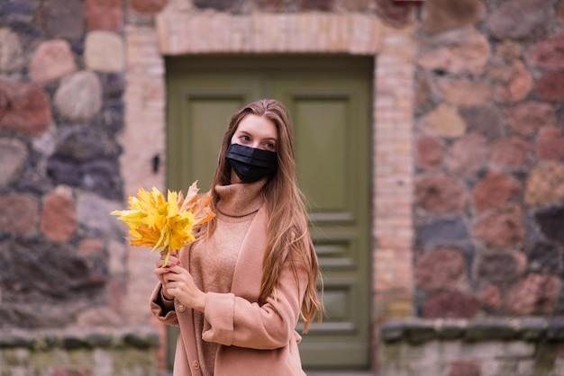 Портрет красивой взрослой молодой женщины на фоне осени в парке в медицинской маске Premium Фотографии