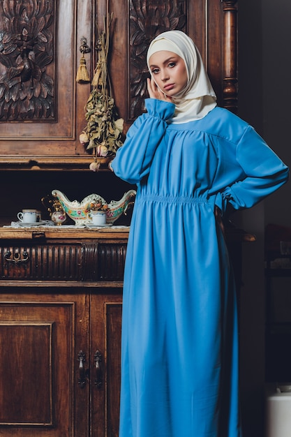 근접 촬영보기에서 배경으로 흰색 커튼에 포즈 흰 블라우스와 파란색 Hijab를 입고 아름다운 아시아 이슬람 여자 모델의 초상화 프리미엄 사진