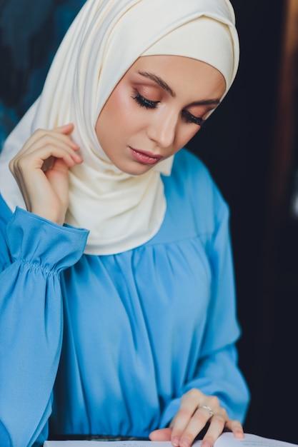 Портрет красивой азиатской мусульманской женщины-модели в белой блузке и синем хиджабе, позирующей на белом занавесе в качестве фона крупным планом Premium Фотографии