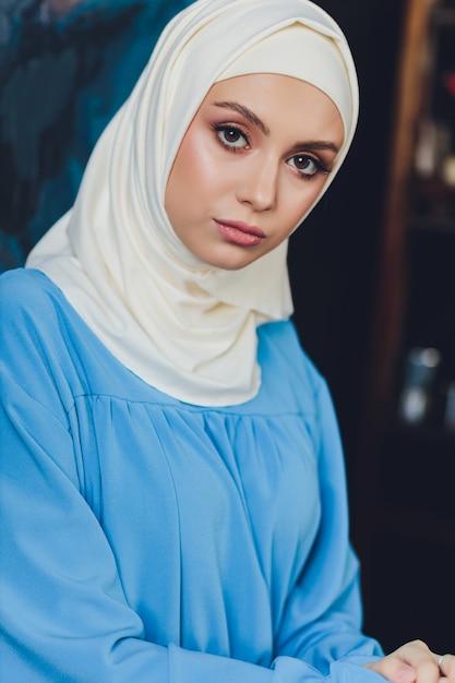 クローズアップビューの背景として白いカーテンにポーズをとって白いブラウスと青いヒジャーブを身に着けている美しいアジアのイスラム教徒の女性モデルの肖像画 Premium写真