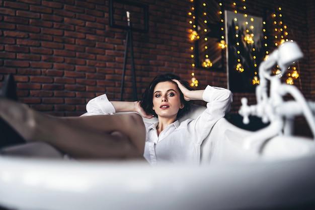 足を持ち上げて空のバスルームに横たわっている美しいブルネットの肖像画 Premium写真