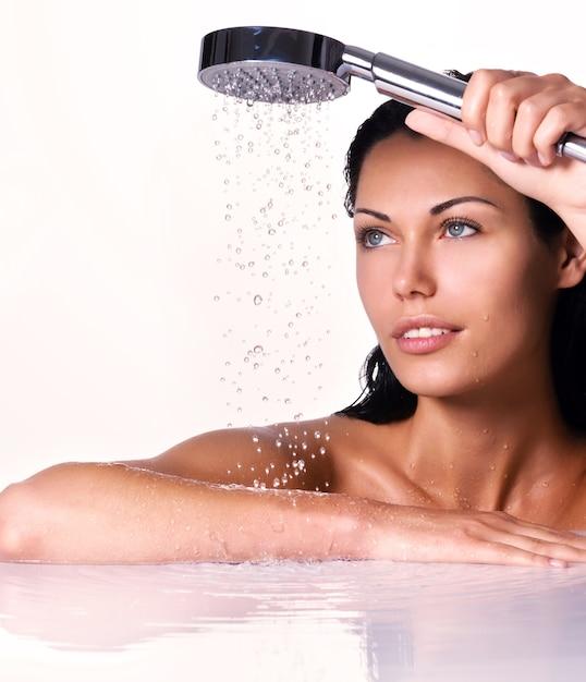 美しいブルネットの女性の肖像画は、水が落ちると手にシャワーを保持します。 無料写真