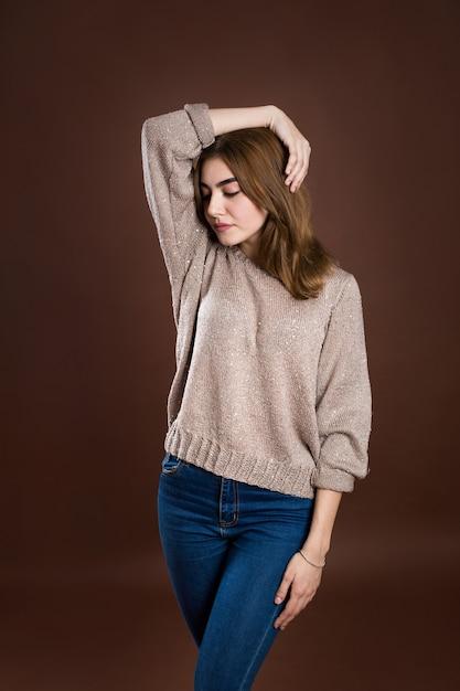 갈색 바탕에 스웨터에 아름 다운 여자의 초상화 프리미엄 사진