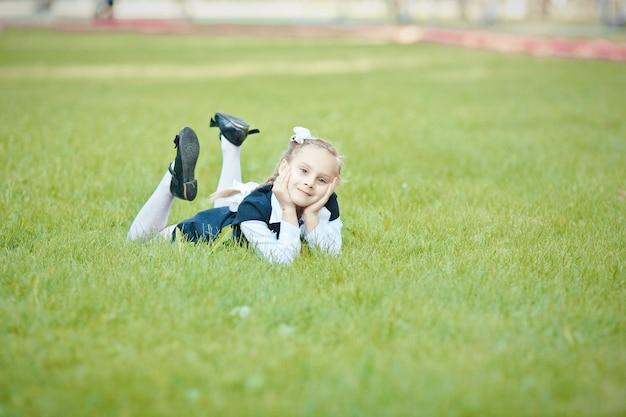 공원에서 테 녹색 잔디에 누워 피그와 흰 나비와 함께 아름다운 여고생의 초상화 프리미엄 사진