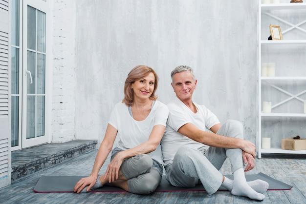 自宅でヨガマットの上に座って美しい笑顔の年配のカップルの肖像画 無料写真