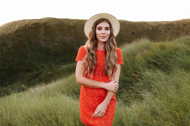 필드에 푸른 잔디에서 빨간 드레스에 아름 다운 여자의 초상화 프리미엄 사진