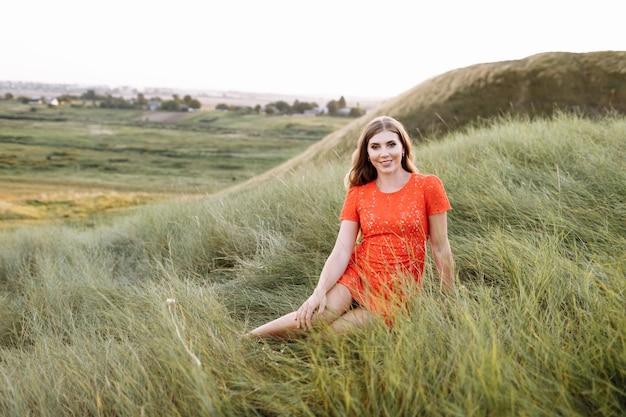 아름 다운 여자의 초상화는 필드에 푸른 잔디에 앉아있다 프리미엄 사진