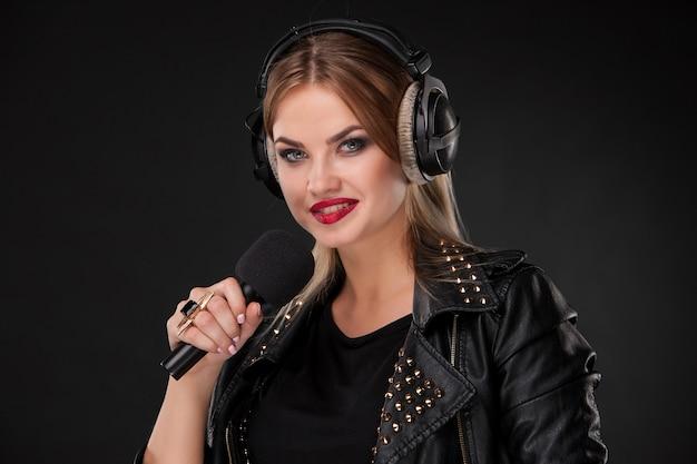 黒の背景のスタジオでヘッドフォンでマイクに向かって歌う美しい女性の肖像画 無料写真