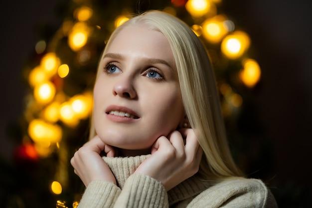 장식 된 크리스마스 트리 근처에 금발 머리를 가진 아름 다운 여자의 초상화, 그녀는 흰색 니트 스웨터를 입고 프리미엄 사진