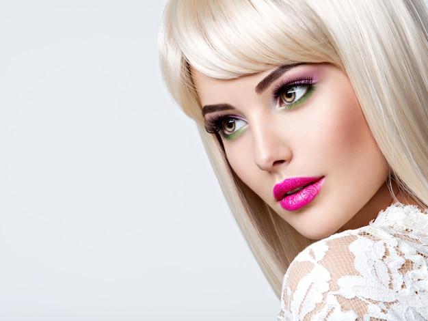 흰색 직선 머리카락과 분홍색 눈 화장과 아름 다운 여자의 초상화. 핑크 립스틱과 패션 모델의 얼굴. 예쁜 여자 포즈입니다. 무료 사진