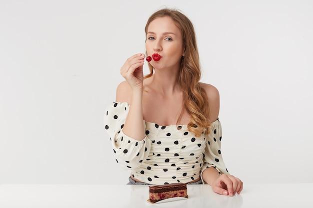 Портрет красивой молодой голубоглазой блондинки с красными губами в платье в горошек. сидящий за столом собирается съесть вишенку с торта. изолированные на белом фоне. Бесплатные Фотографии