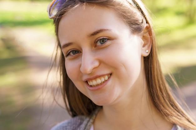 Портрет красивой молодой девушки с серьгой в ухе, которая улыбается в камеру в солнечный день Бесплатные Фотографии