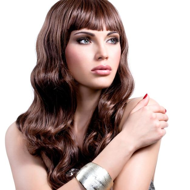 Портрет красивой молодой женщины с длинными каштановыми волосами. симпатичная девушка-модель со стильной бижутерией серебристого цвета. Бесплатные Фотографии