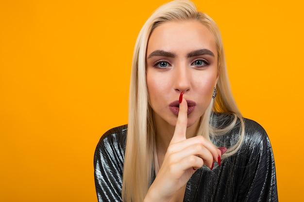 Портрет молодой блондинки, просящей быть тише в желтой студии Premium Фотографии