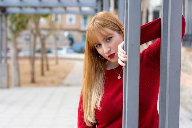 주거 분기에 빨간 립스틱과 빨간 스웨터와 금발 소녀의 초상화 프리미엄 사진