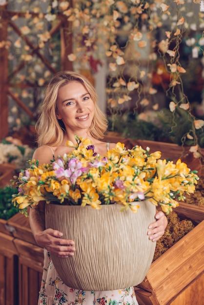 黄色の花で大きな鍋を保持している金髪の笑顔若い女性の肖像画 無料写真