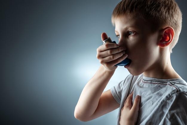 喘息吸入器を使用して炎症性疾患、息切れを治療する少年の肖像画。咳、アレルギー、気道疾患の治療の概念。 Premium写真