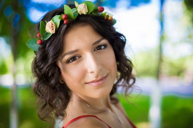 Портрет брюнетки с цветами в волосах в зеленом парке. Premium Фотографии