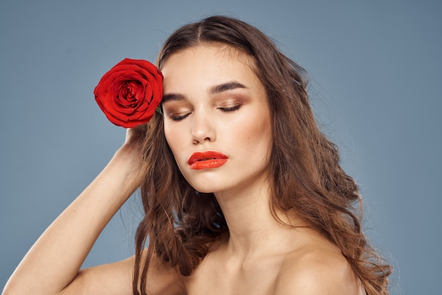 Портрет брюнетки с красной помадой на губах, красивая женщина с розой Premium Фотографии