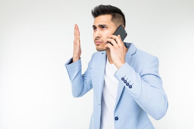 Портрет бизнесмена в синем пиджаке с неудовольствием разговаривает по телефону по важным вопросам. Premium Фотографии