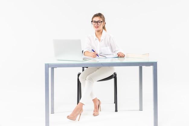 白い背景で隔離のラップトップで机に座っている実業家の肖像画 無料写真