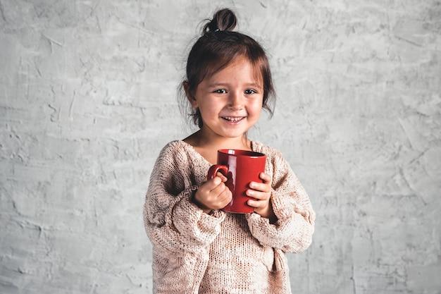 Портрет очаровательной маленькой девочки в бежевом свитере на сером фоне Premium Фотографии