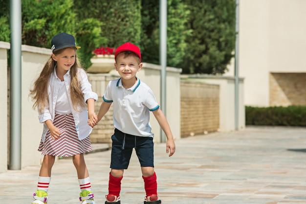 公園でローラースケートで一緒にスケートをする魅力的な10代のカップルの肖像画。 10代の白人の男の子と女の子。子供たちのカラフルな服、ライフスタイル、流行色の概念。 無料写真