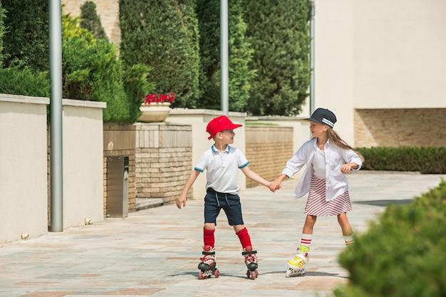 公園でローラースケートで一緒にスケートをする魅力的な10代のカップルの肖像画。 10代の白人の男の子と女の子 無料写真