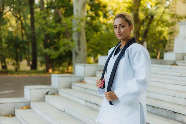 Портрет жизнерадостной женщины-бойца в белых кимоно с черным поясом на открытом воздухе Premium Фотографии