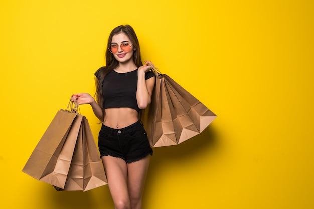 夏の帽子と黄色の壁に買い物袋を保持しているサングラスで陽気な若いブロンドの女性の肖像画 無料写真