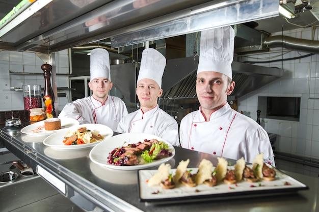 Портрет шеф-повара с приготовленной едой на кухне в ресторане. Premium Фотографии