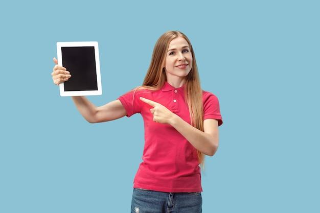 ノートパソコンの分離された壁の空白の画面を示す自信を持ってカジュアルな女性の肖像画 無料写真