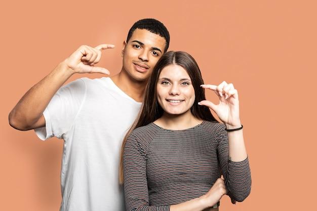 Портрет пары, показывающей маленькие размеры с пальцами в футболках на оранжевом фоне Premium Фотографии