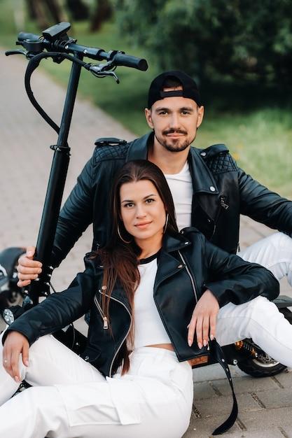 電動スクーターの近くに座って、一緒に自然の中で時間を楽しんでいるカップルの肖像画、電動スクーターの2人の恋人。スクーターの人々。 Premium写真