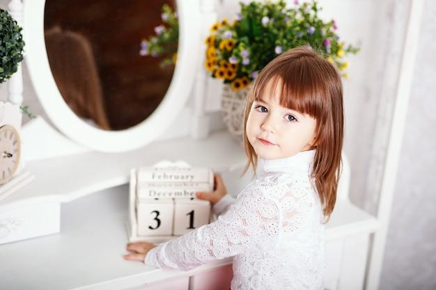 ぼろぼろのシックな装飾が施されたインテリアの手に木製のカレンダーと鏡の近くに座っているかわいい女の子の肖像画 Premium写真