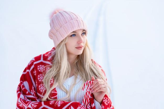 Портрет милой женщины на фоне снега в розовой шляпе и красном пледе позирует на камеру Бесплатные Фотографии