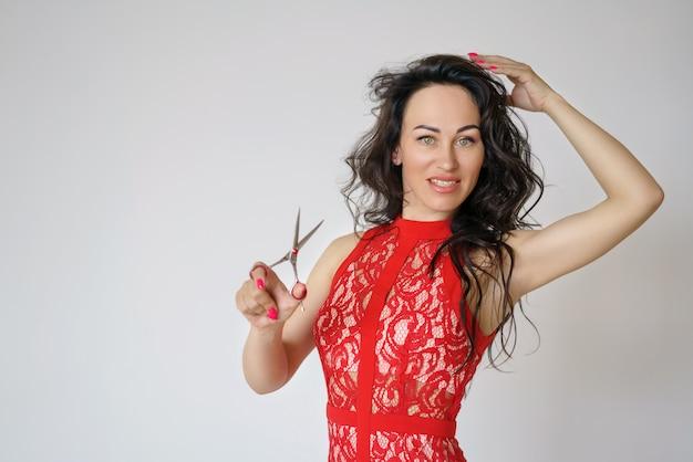 Портрет милой женщины в красном платье с длинными волосами, держащей в руке ножницы на свету Бесплатные Фотографии