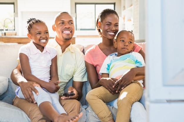 Портрет семьи из четырех смотрящих телевизор Premium Фотографии