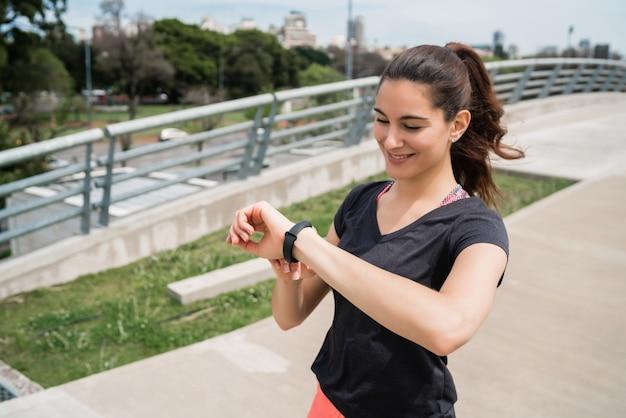 スマートウォッチで時間をチェックするフィットネス女性の肖像画。スポーツと健康的なライフスタイルのコンセプト。 無料写真