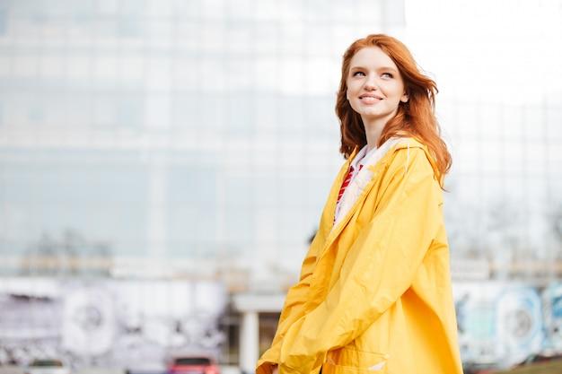 Портрет дружелюбной довольно рыжеволосой девушки в пальто Premium Фотографии