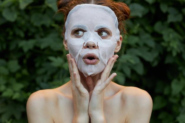 女の子のフェイスマスクのポートレート手で顔を触る透明肌 Premium写真