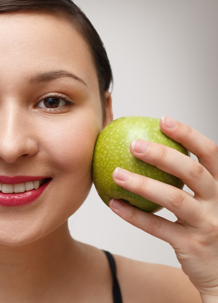 Портрет девушки с половиной лица с яблоком, прислонившимся к щеке. на сером фоне Premium Фотографии