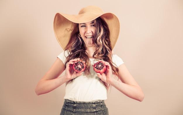 色付きの背景にフルーツと夏帽子の少女の肖像画 無料写真