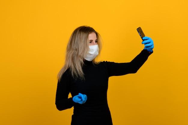黄色の背景に医療マスクを着ている少女の肖像画 Premium写真
